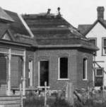 this house being built ca 1909, workers on the roof in this photo, curved porch not added yet.